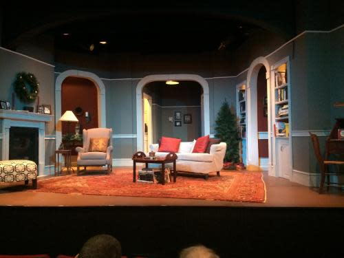 Photo of a stage set of a theater production at Ghent Playhouse. The set looks like a living room with sofa, chair, area rug, table and arched openings to other non-visible rooms.