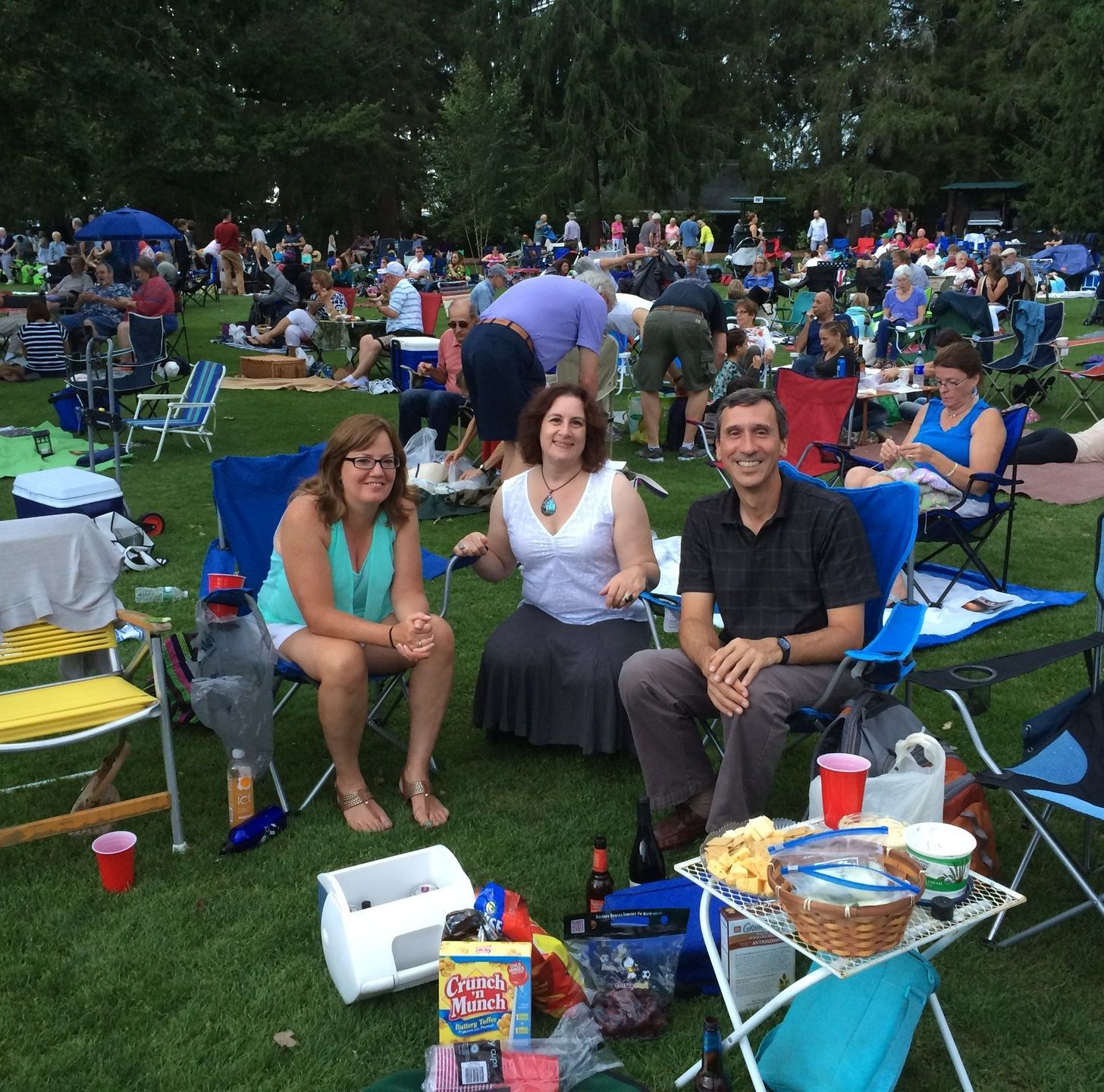 A photo of three smiling people picnicking on the lawn at Tanglewood.  Many lawn chairs, small tables, and blankets with people can be seen in the background.