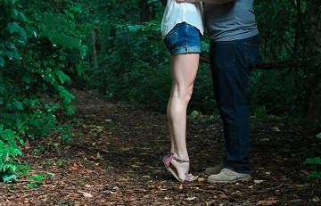 Legs of couple embracing with woods background