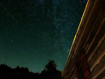 Starry night sky outside of log house at Sugar Tree Inn