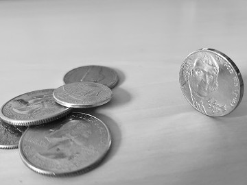 black and white image of coins with balanced nickle