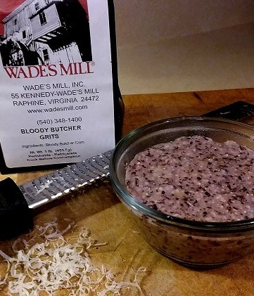 Bag of Wade's Mill's Bloody Butcher Grits with bowl of grits and grater on wood cutting board