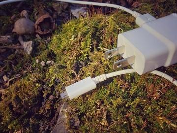 A White Phone Plug outside on moss