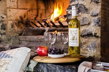 Picnic basket and wine in front of a woodburning fireplace