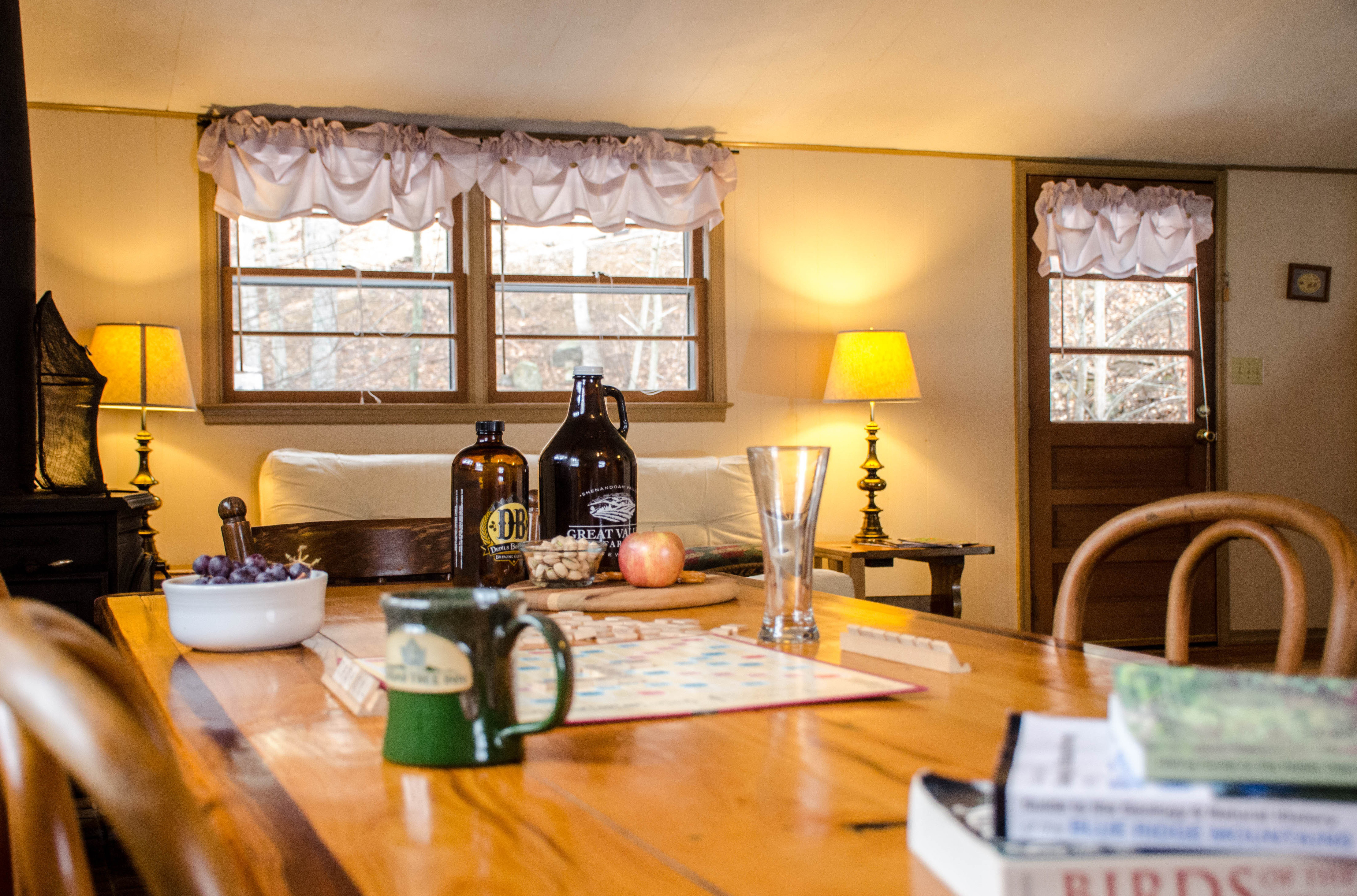 Creek House with Devils Backbone and Great Valley Farms growlers on table with Scrabble Game out