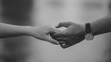 black-and-white photo of holding hands