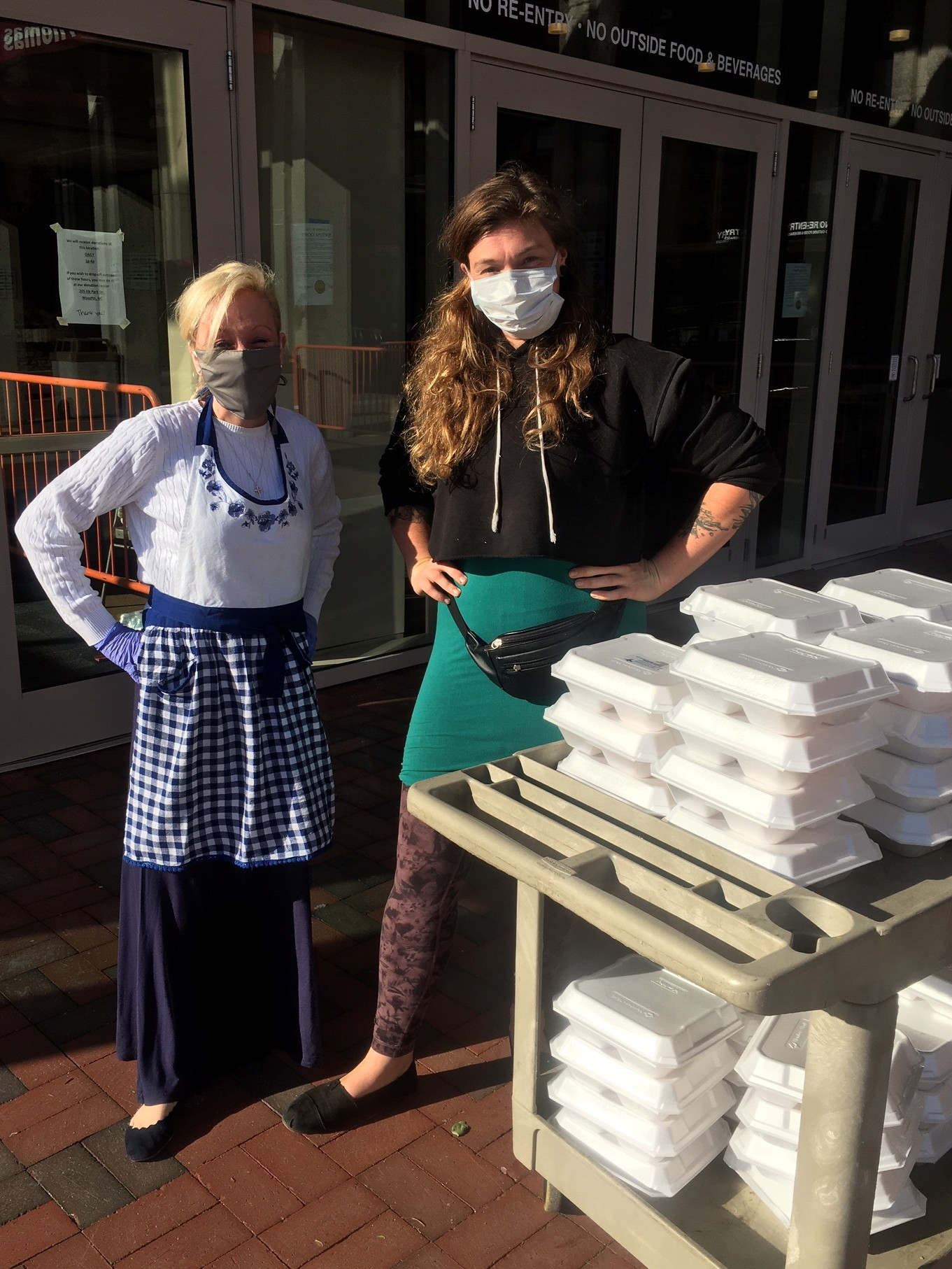 two people will cart full of meal for homeless in Asheville