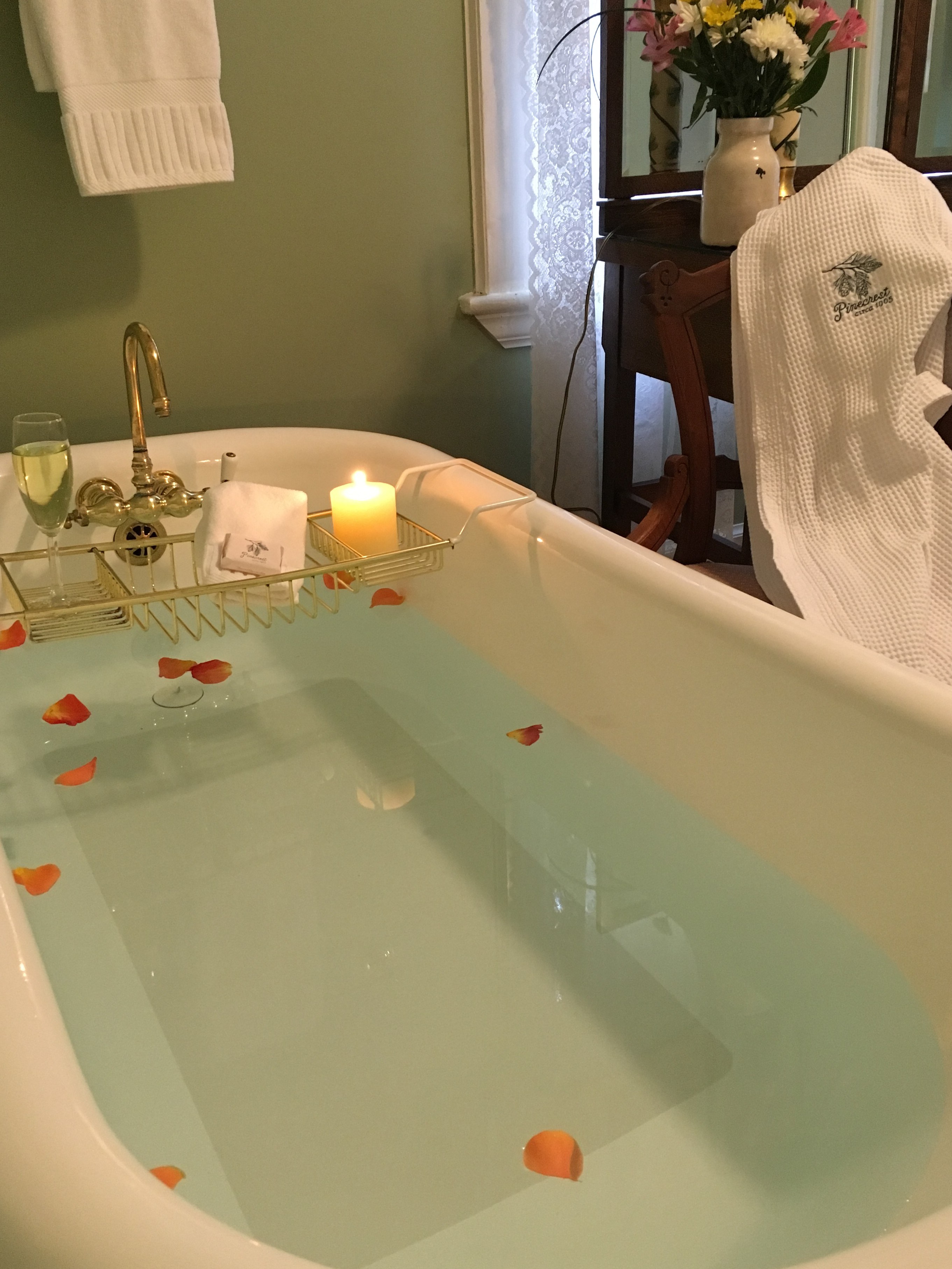 romantic clawfoot bathtub at b&b with rose petals