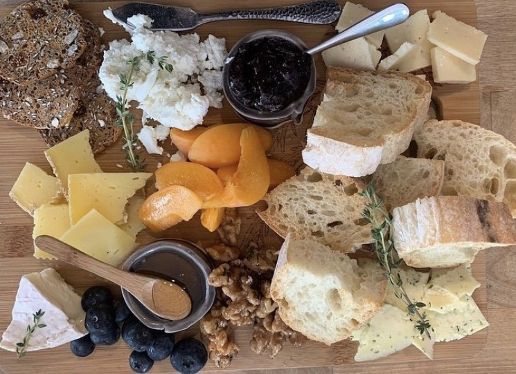rustic grape cheese board with nuts, fruits, baguettes