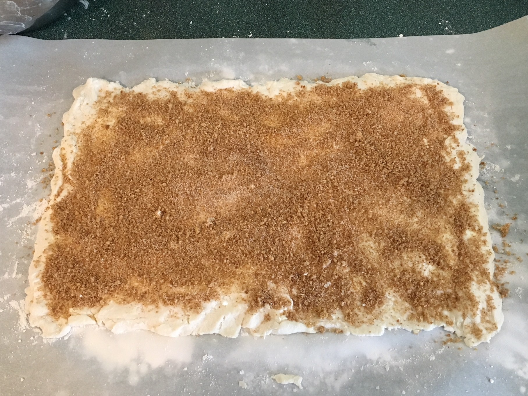 biscuit dough rolled into rectangle with sprinkle cinnamon sugar
