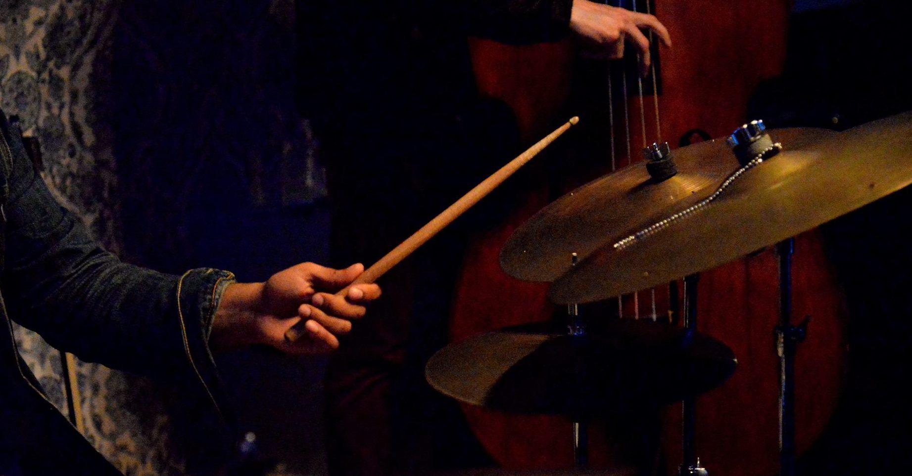 Jazz band featuring drummer holding drumsticks