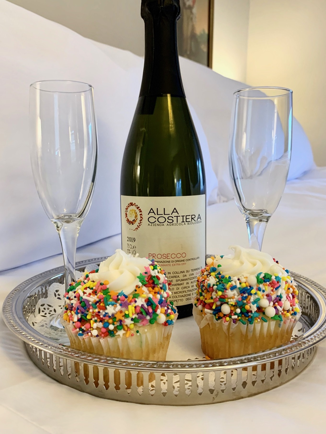 tray with bottle of prosecco, glasses, and 2 birthday cupcakes on a bed