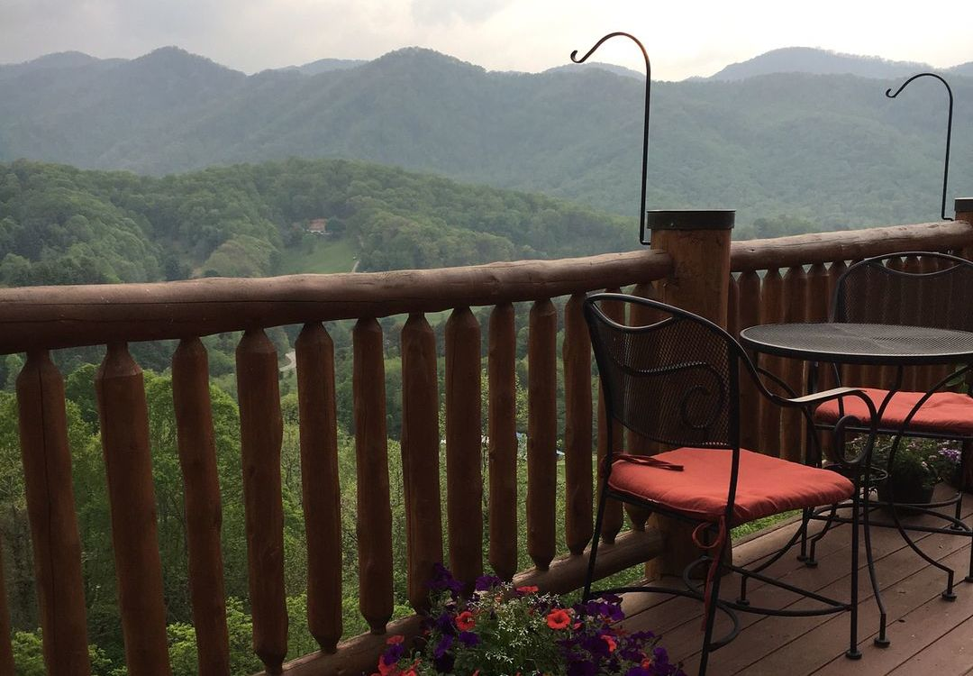 outdoor chair set on deck with green rolling mountains