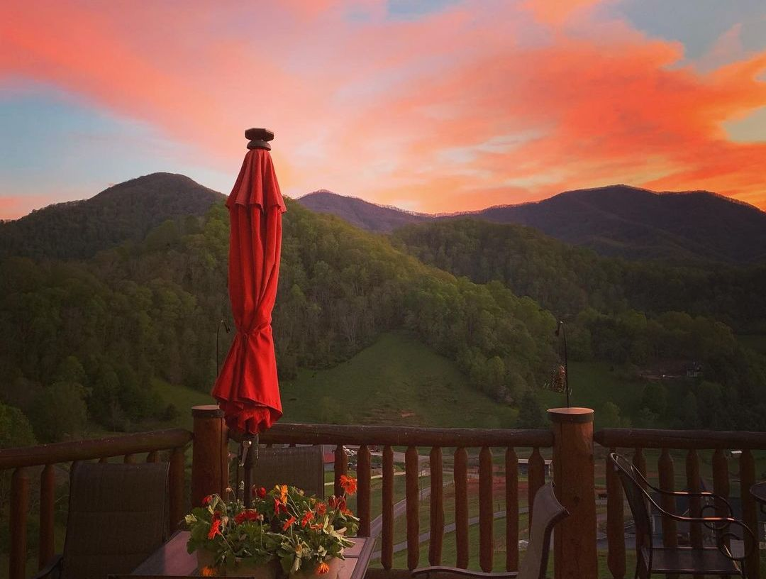 sunset over rolling green hills red umbrella and red flowers