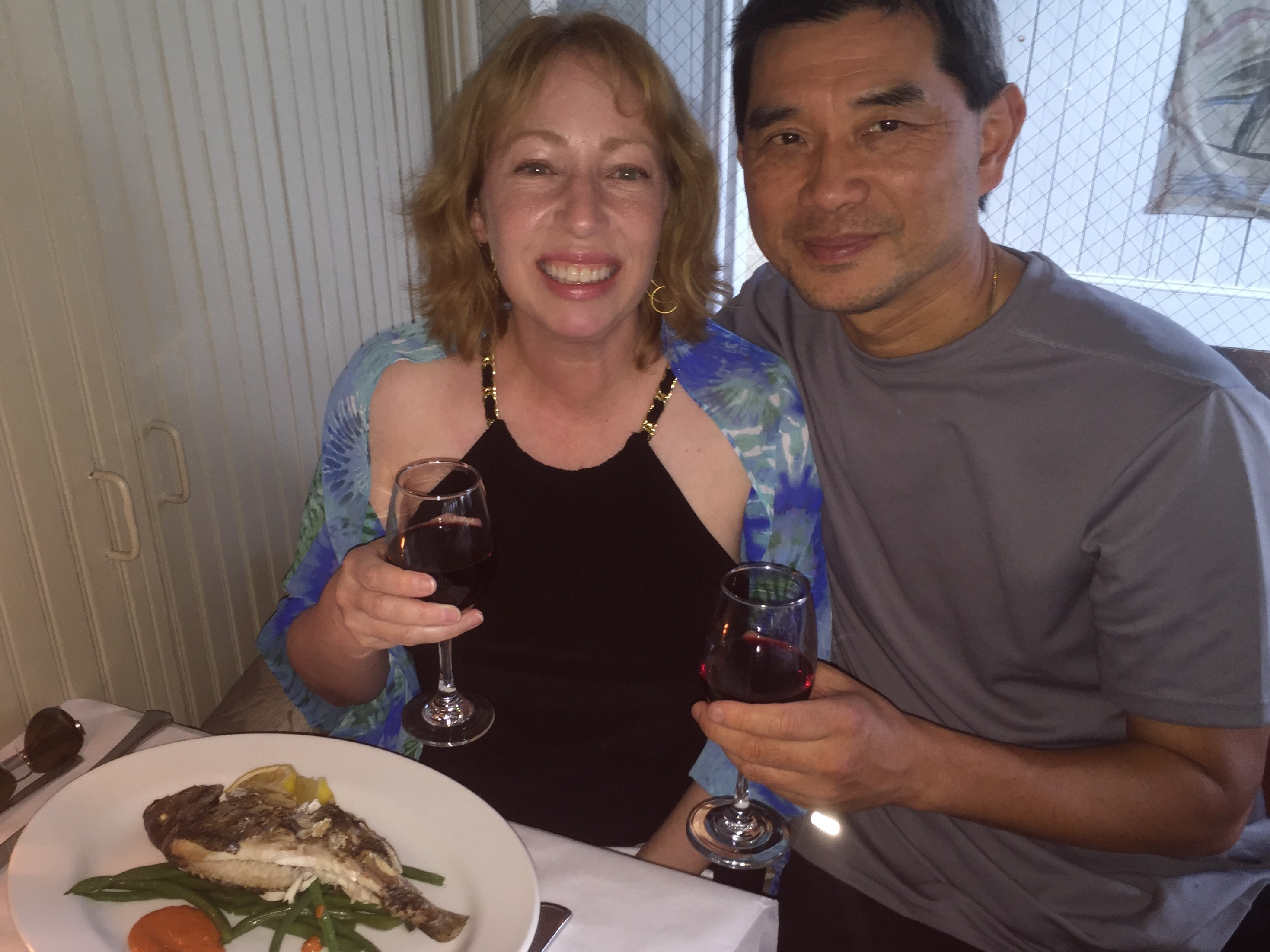 Happy couple at a table with wine in hand and a plate of fish and vegetables