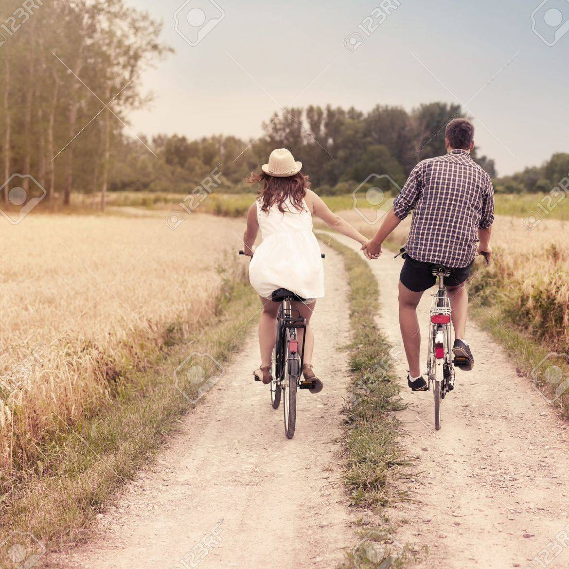 couple riding a bike on a countryside bike path w greenery and they are riding side by side holding hands. She has a straw hat on.