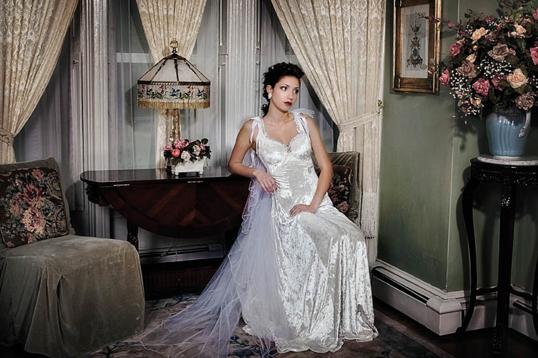Bride with updo sitting in parlor next to table and glass lamp in a bay window