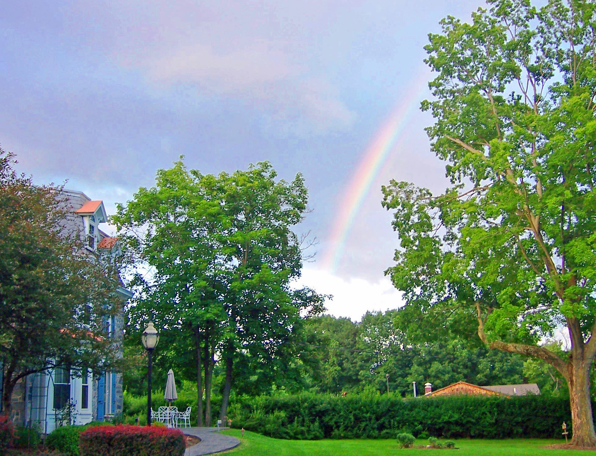 rainy cloudy sky and a rainbow in front of the inn and lawn