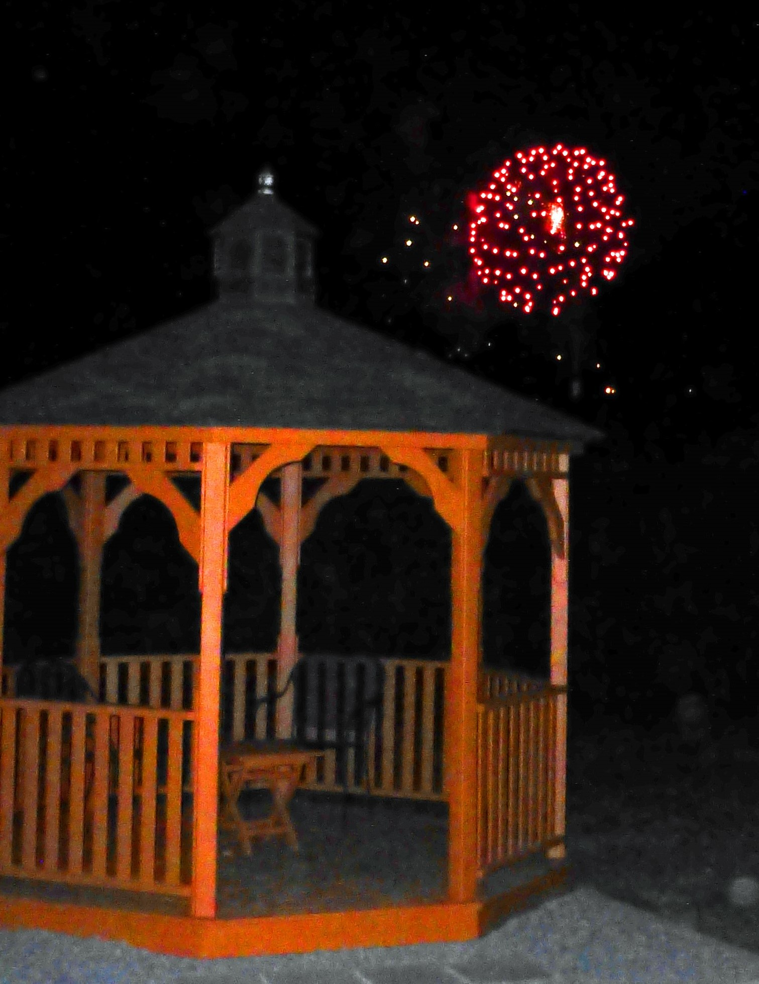 Fireworks exploding red crystals over the gazebo