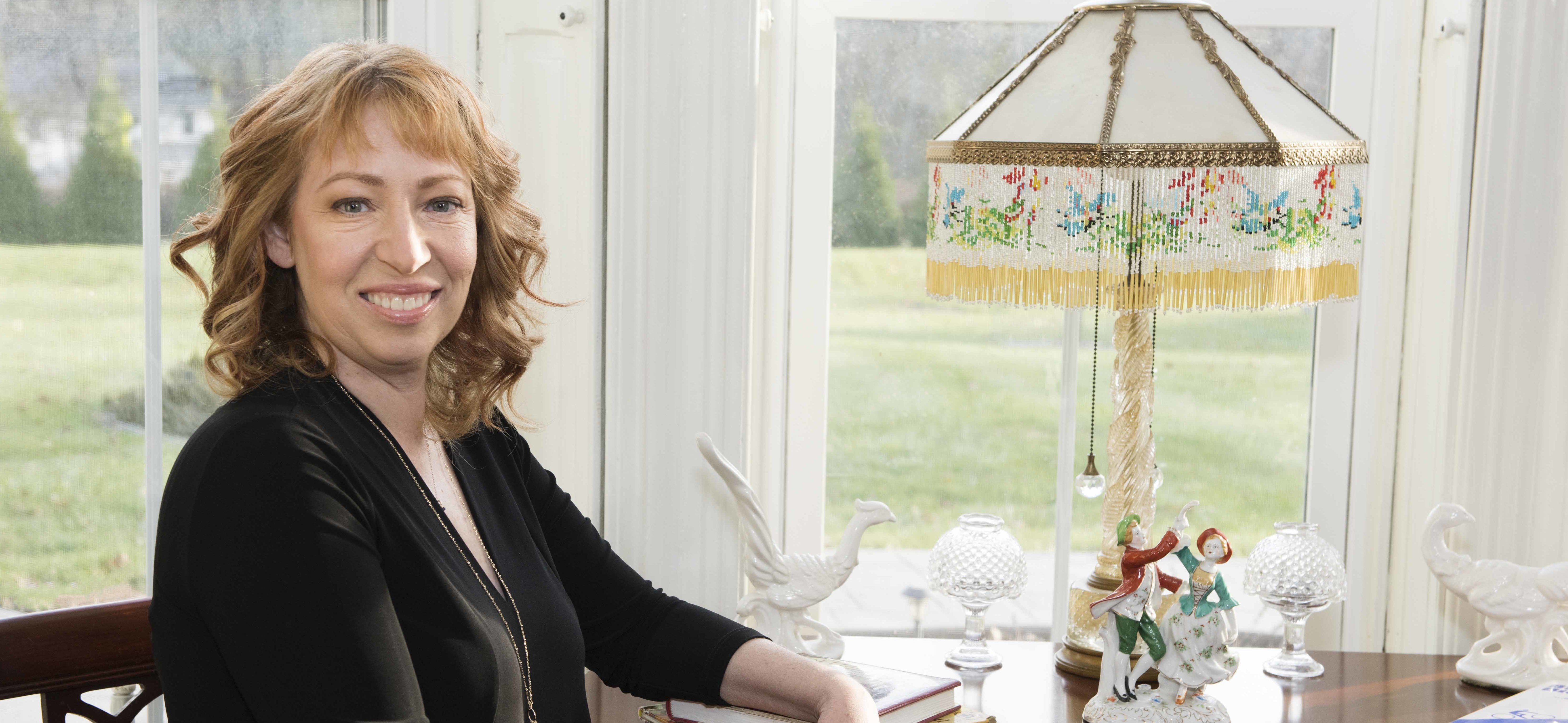 lisa sitting in front of window with recipe books and antique lamp