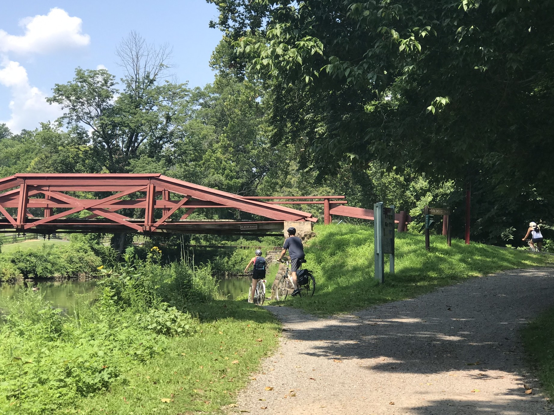 red bridge over canal and two people on bikes starting descent to path under bridge