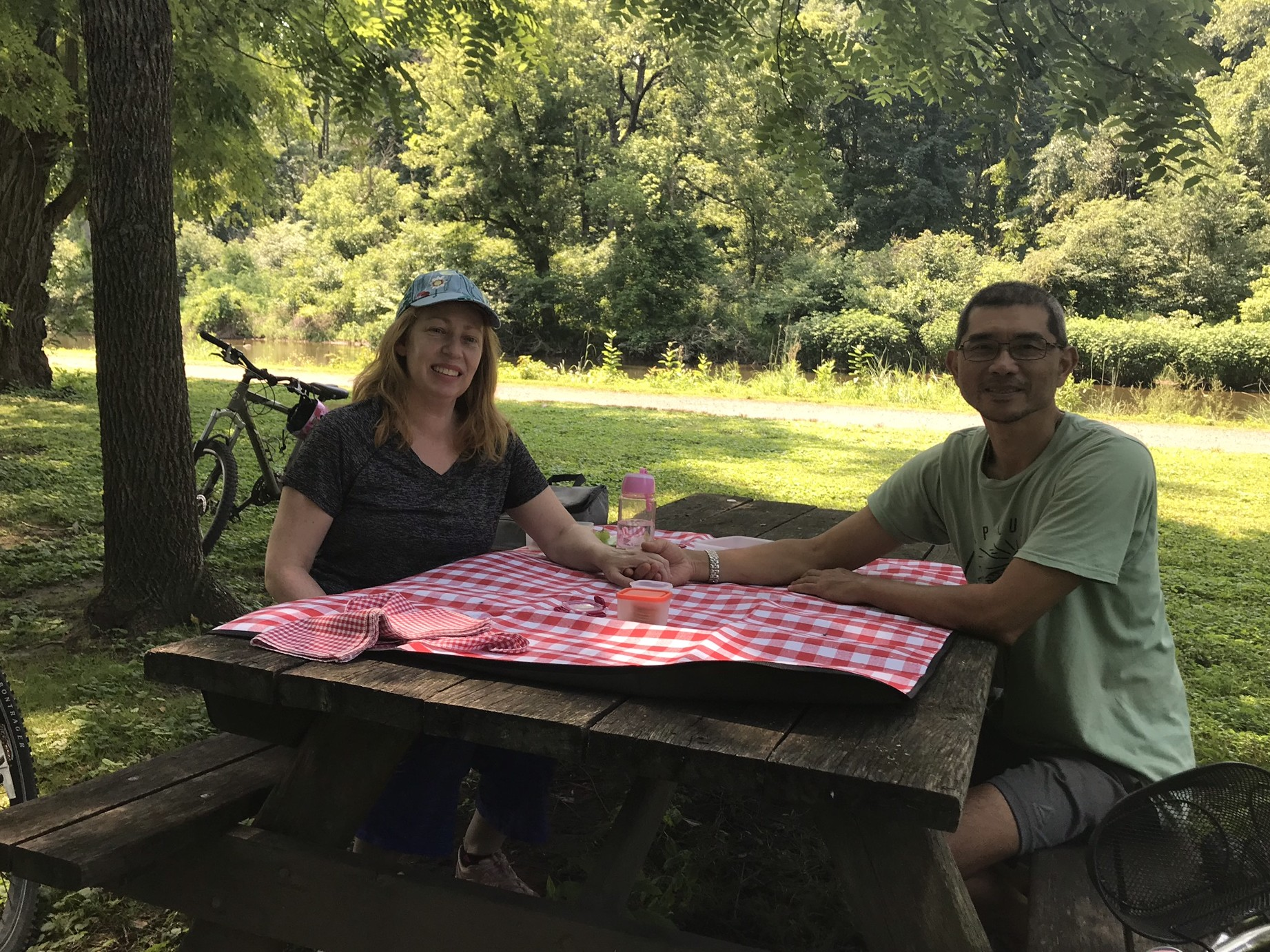 Lisa and mike at picnic table with a red white stripe tablecloth having a picnic and holding hands