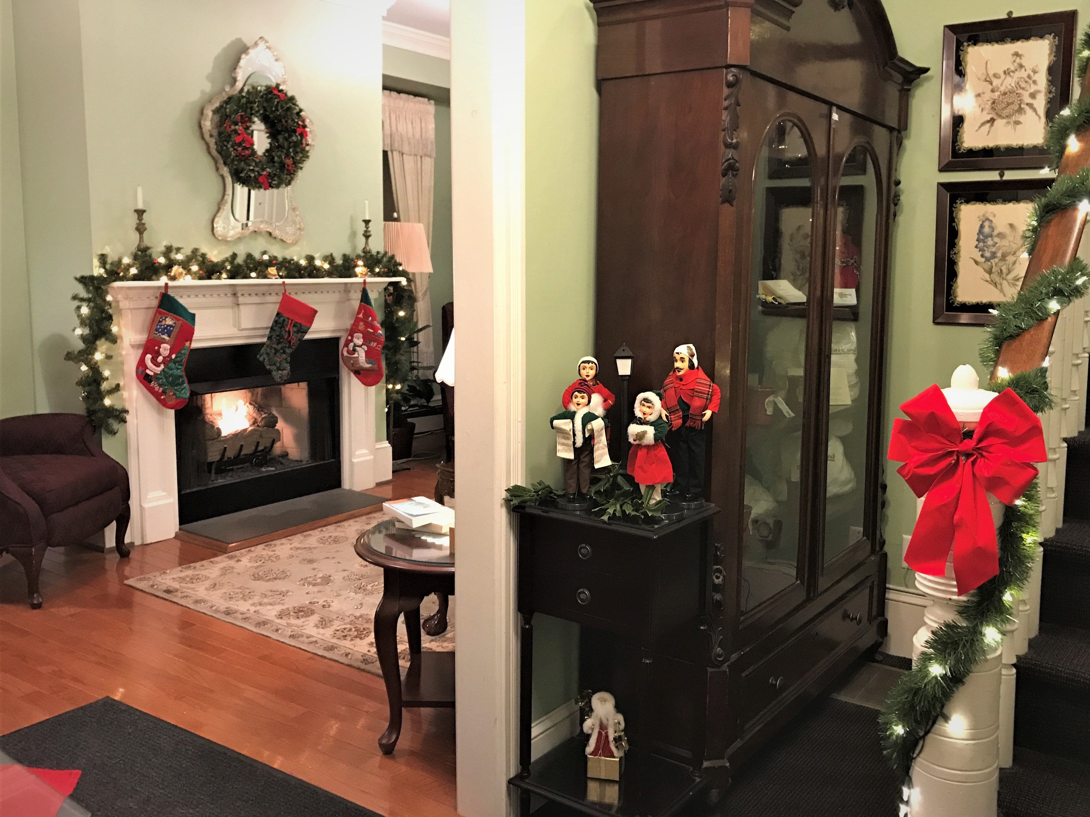 fireplace lit with red stockings hung, viewed from the front door and lights on bannister