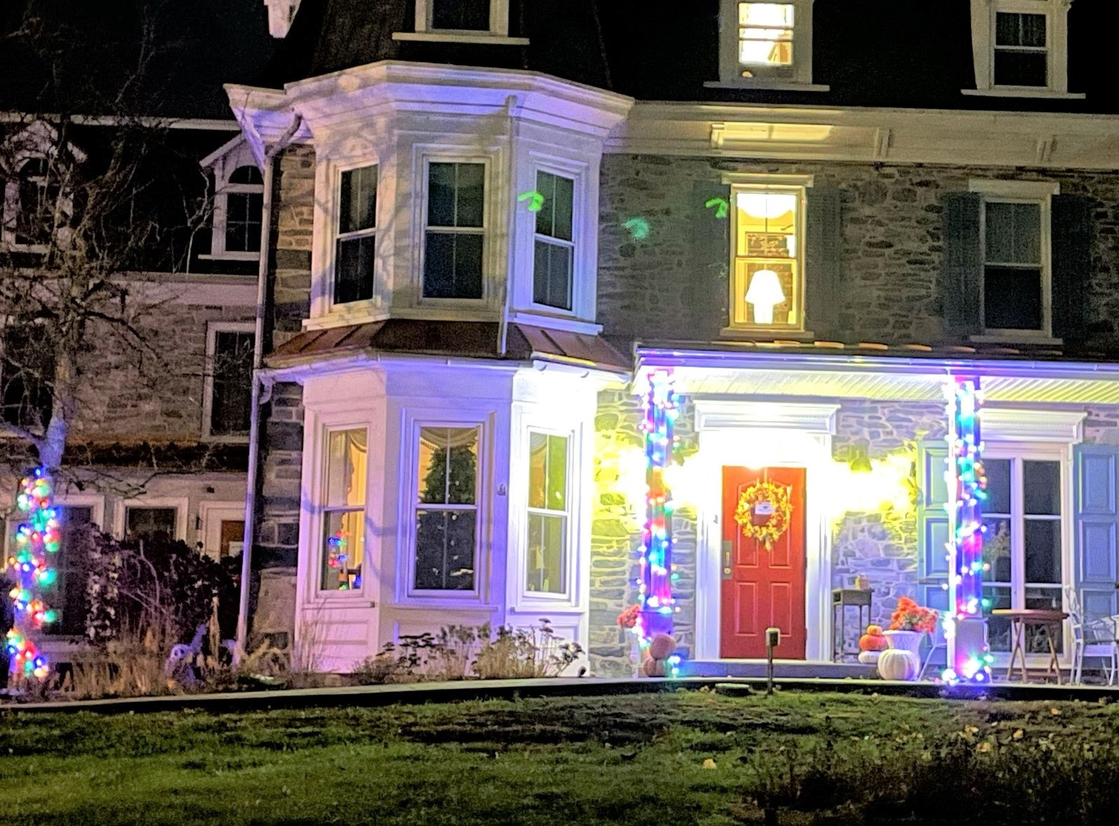 Front of stone manor at night with holiday lights on columns and light shining on welcoming red front door