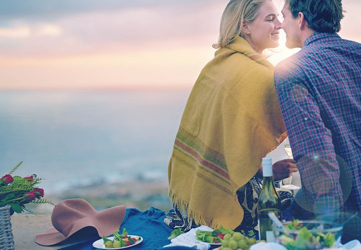 couple sitting in front of water and about to kiss. They are sitting on a picnic blanket with some bowls of fruit