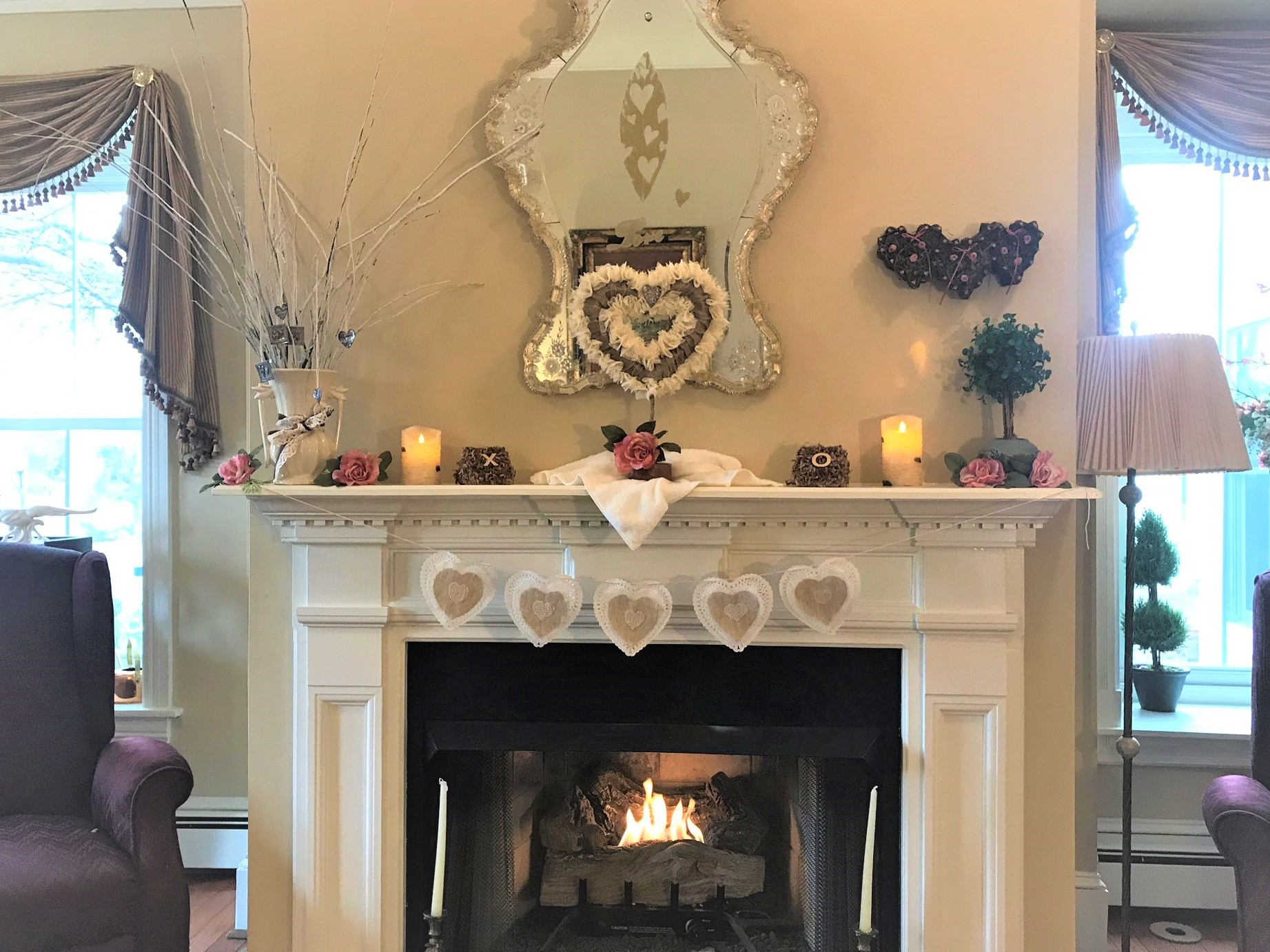 fireplace with a roaring fireplace with a tan heart decoration on mantel and antique mirror with hearts. also a x and an o decoration.