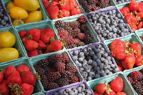 An array of fresh fruits and berries at market