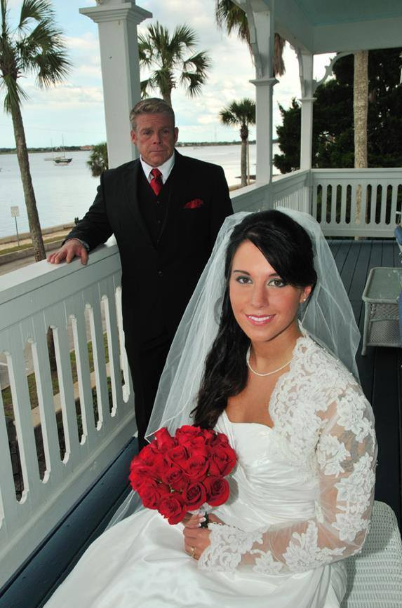 Elopement couple on bayfront balcony, bride in traditional gown