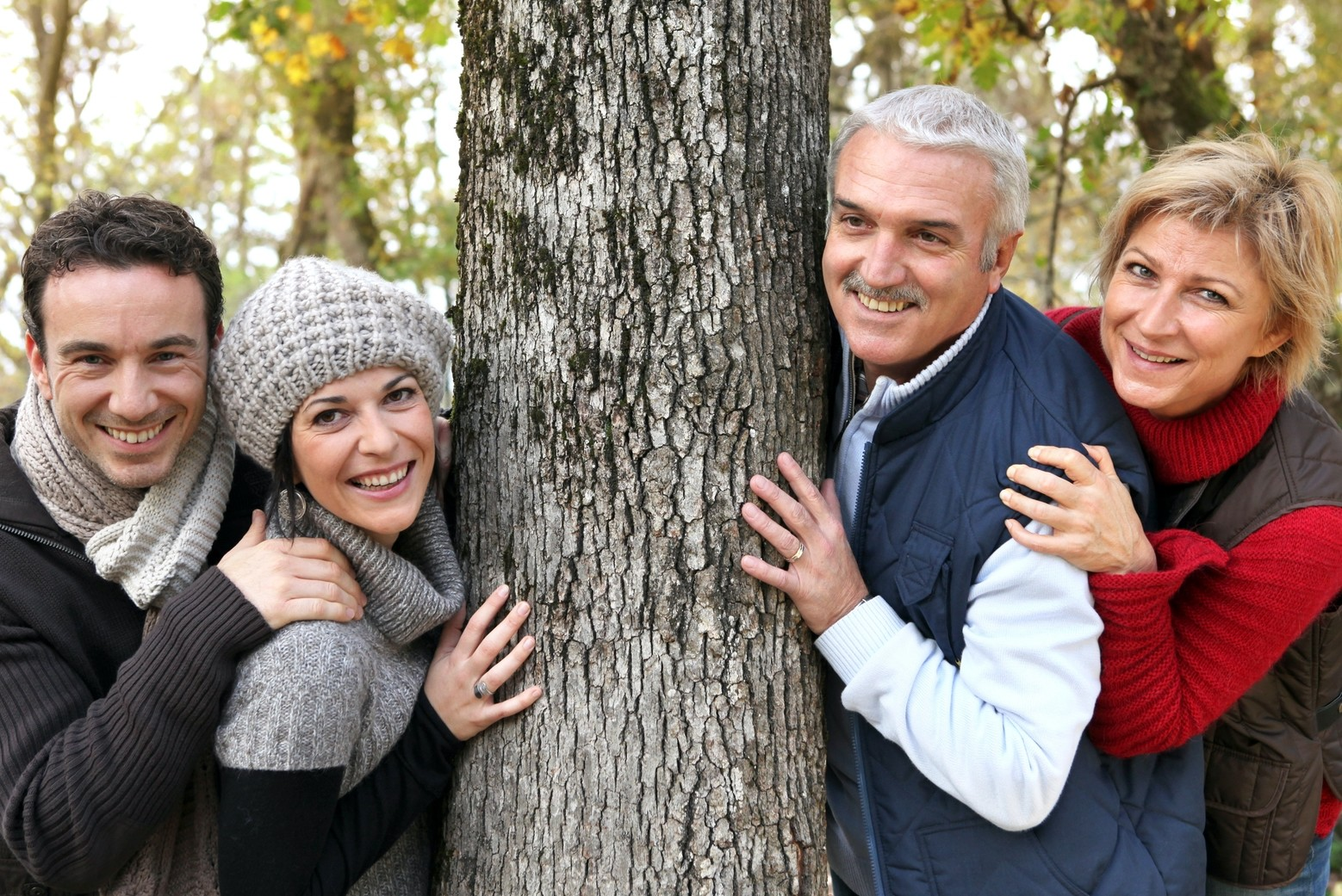 Adult family around tree on returning guest discount