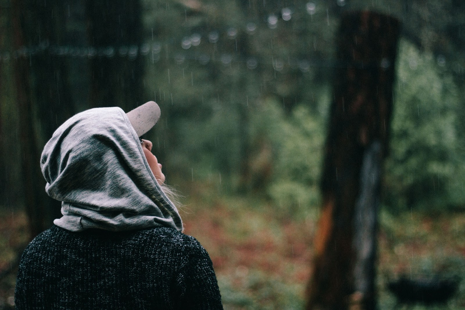 A young woman with a cap and a hood shielding her from a light rain in a wooded area
