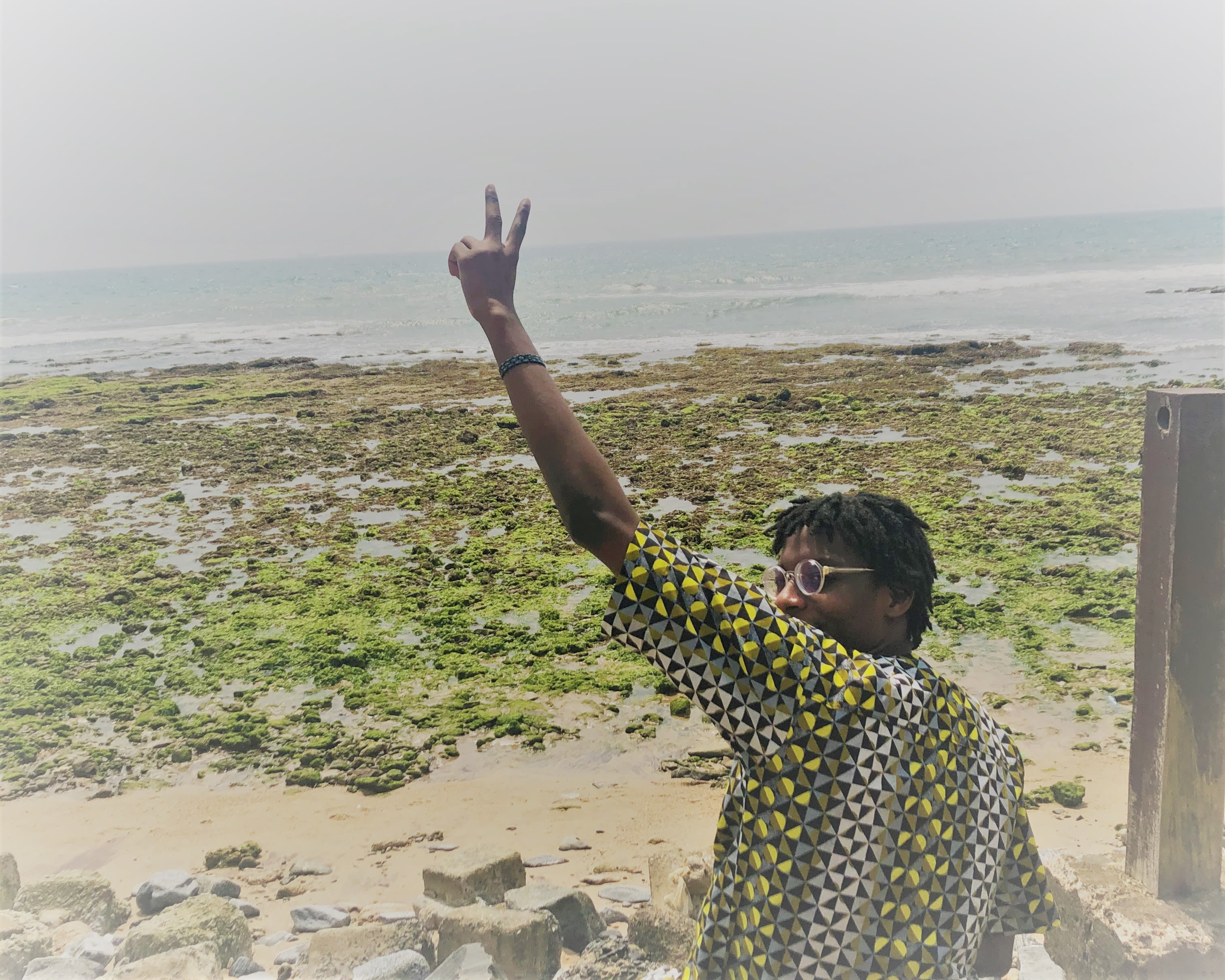 Ore Ogundipe sitting at the beach, throwing a peace sign