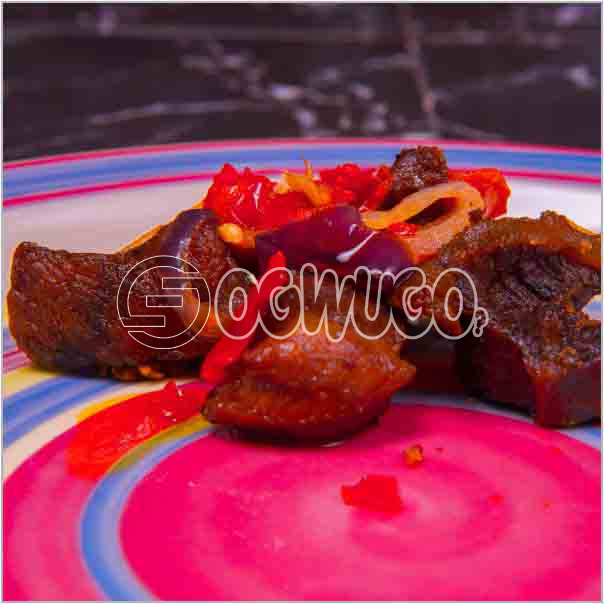 A portion of well sauced and garnished Beef which is made up of two pieces of beef