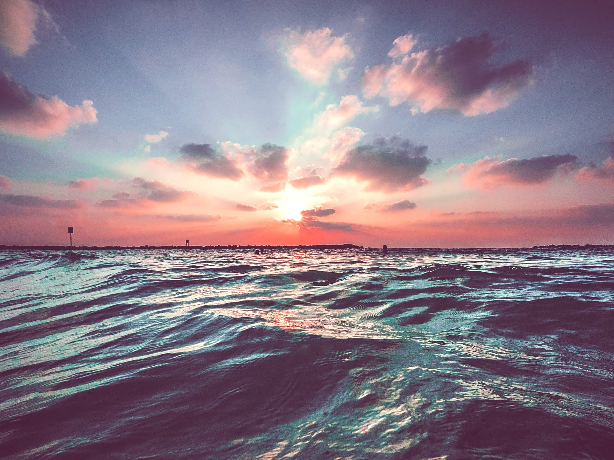 An image of a sunset over a large body of water, by @jbcreate_ on Unsplash.