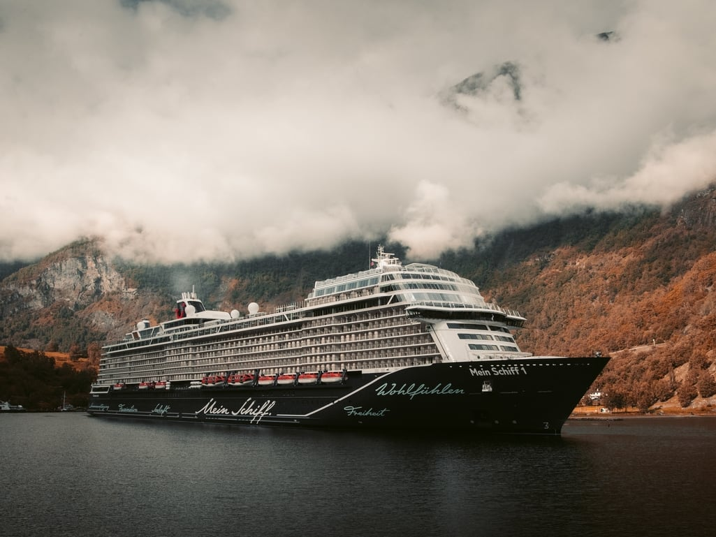 An image of a ship cruising on a river beside a mountain on a cloudy day by @redcharlie on unsplash.