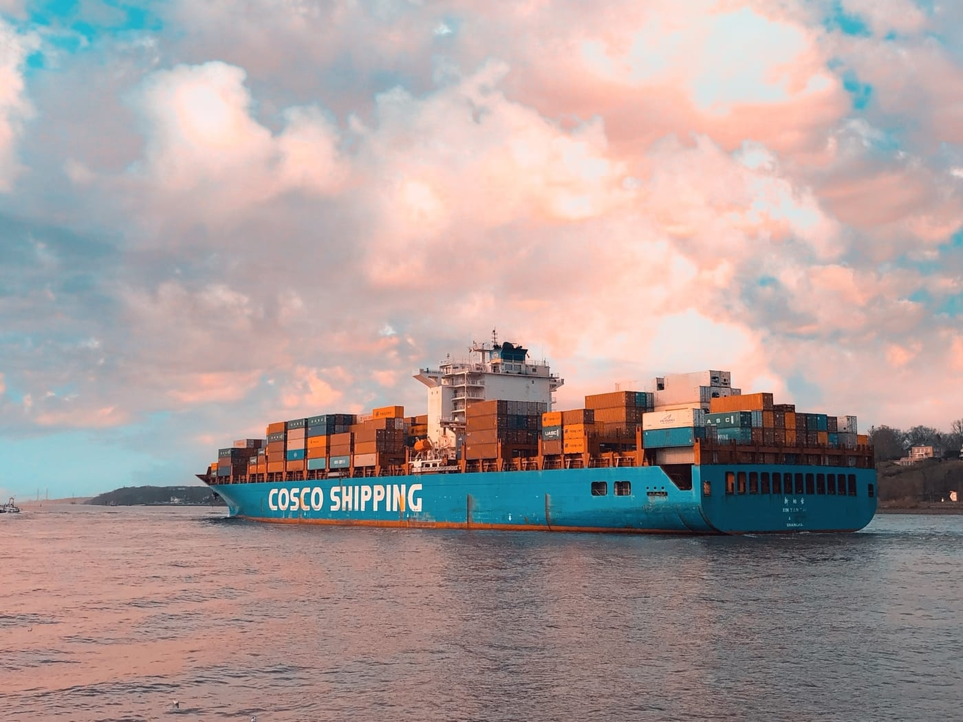 An image of a cargo ship underneath a partially cloudy pink evening sky by @snygo on unsplash.
