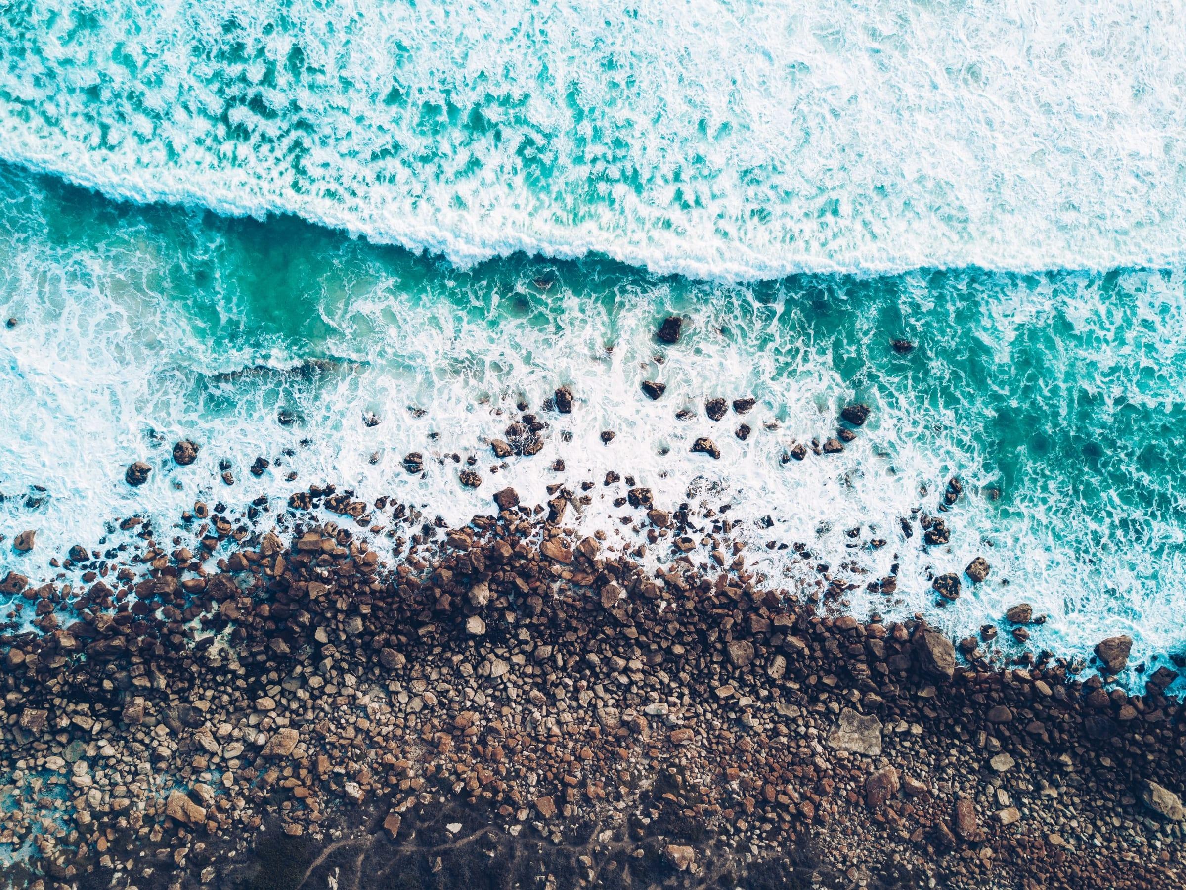 An image of waves hitting the stoney edge of a beach by @johnonolan on unsplash.