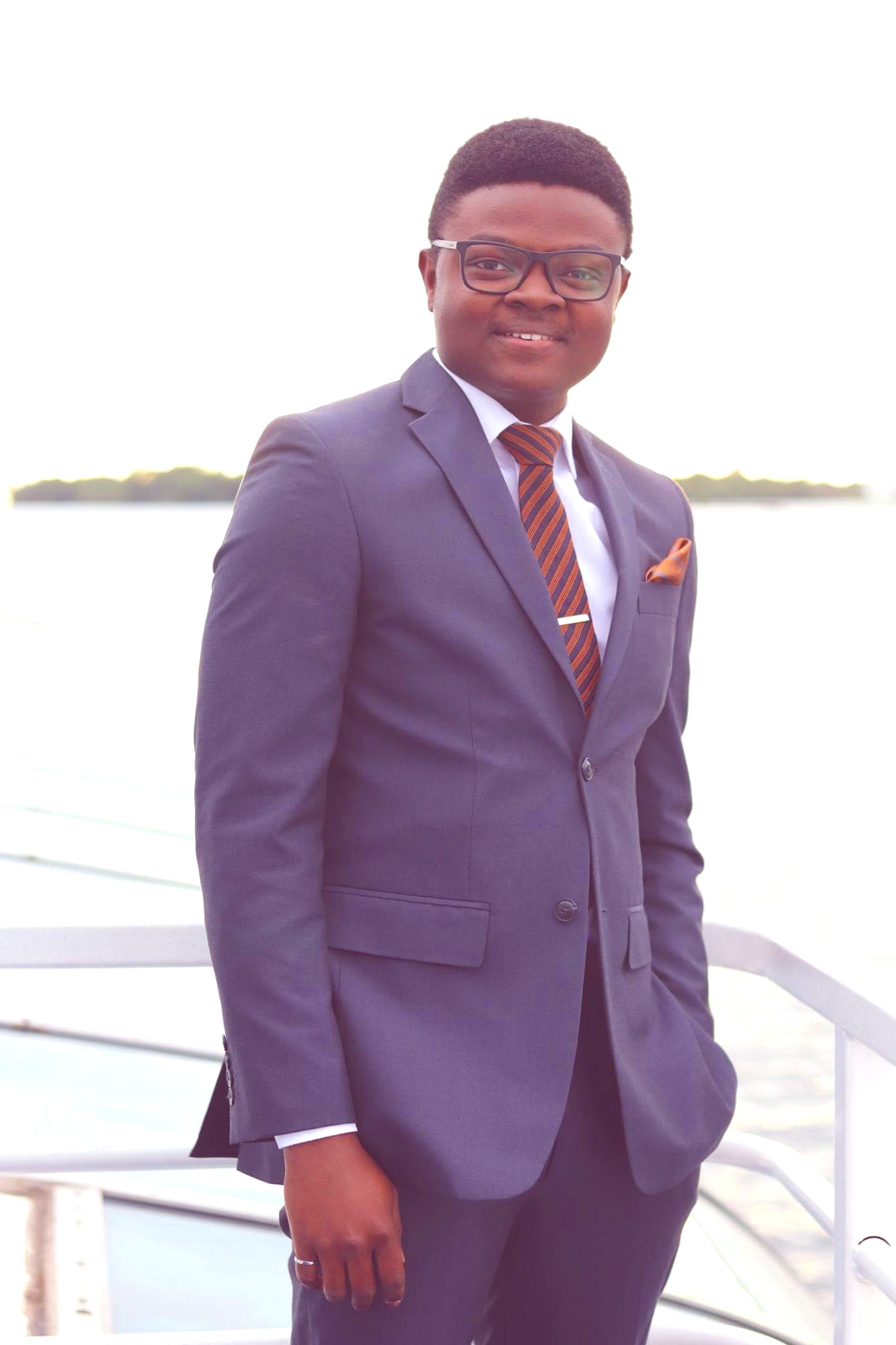 An image of Joseph Ojo in a suit on a boat.