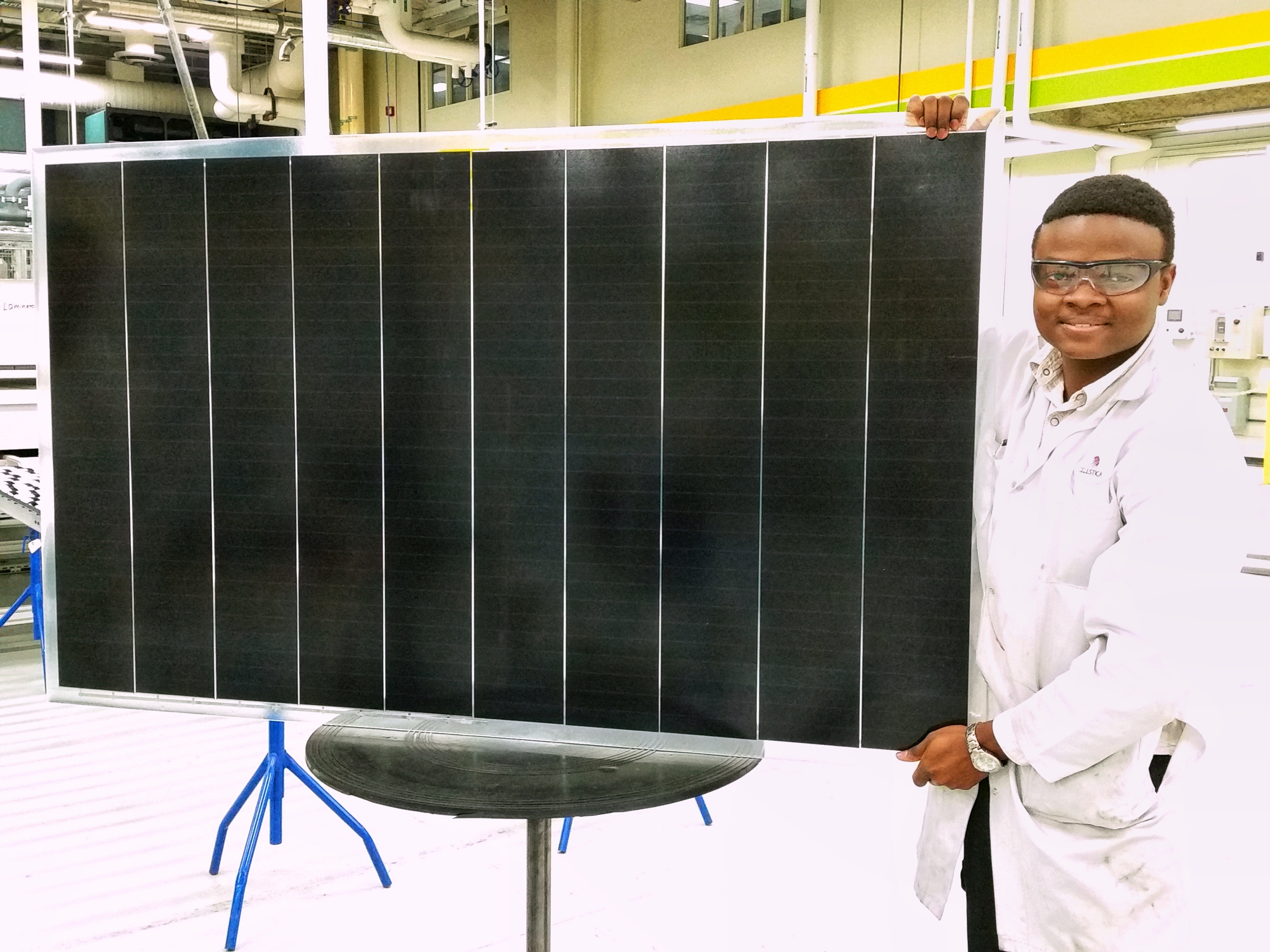 An image of Joseph Ojo holding a large pane of Solar Panels.