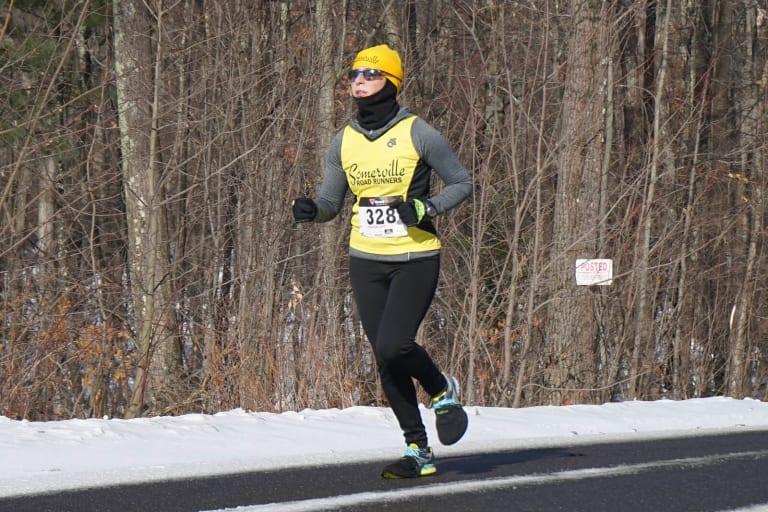 Спортсменка бежит по зимней дороге