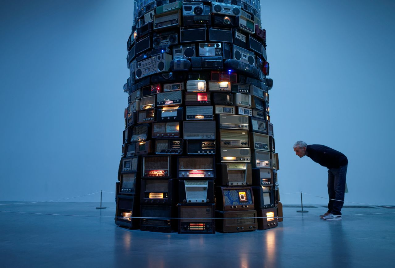 Man leaning in close to a tower built with radio receivers from different eras tuned randomly into a whisper.