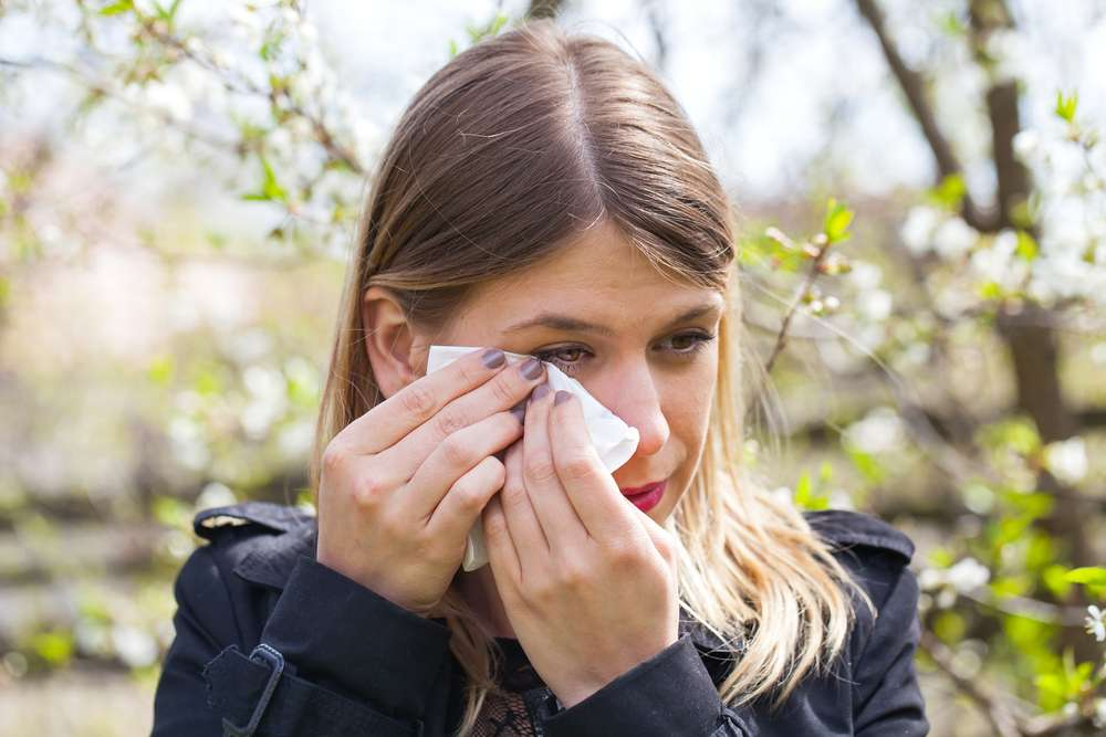 A girl experiencing watery eyes as a symptom of pollen allergy