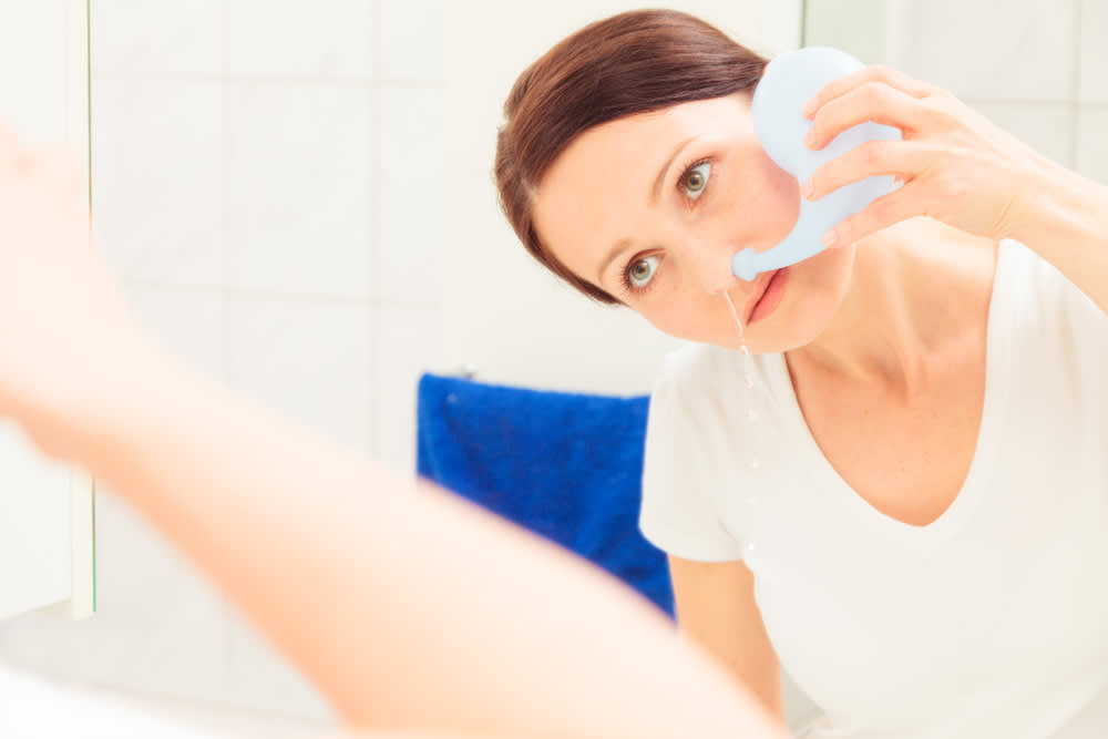 Woman performing nasal irrigation with a neti pot as a treatment for pollen allergy