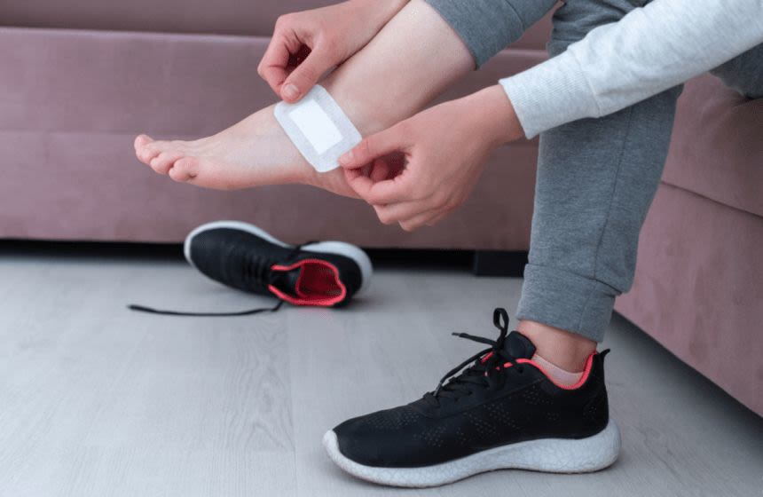 A woman using adhesive bandage to prevent foot corn when wearing new shoes
