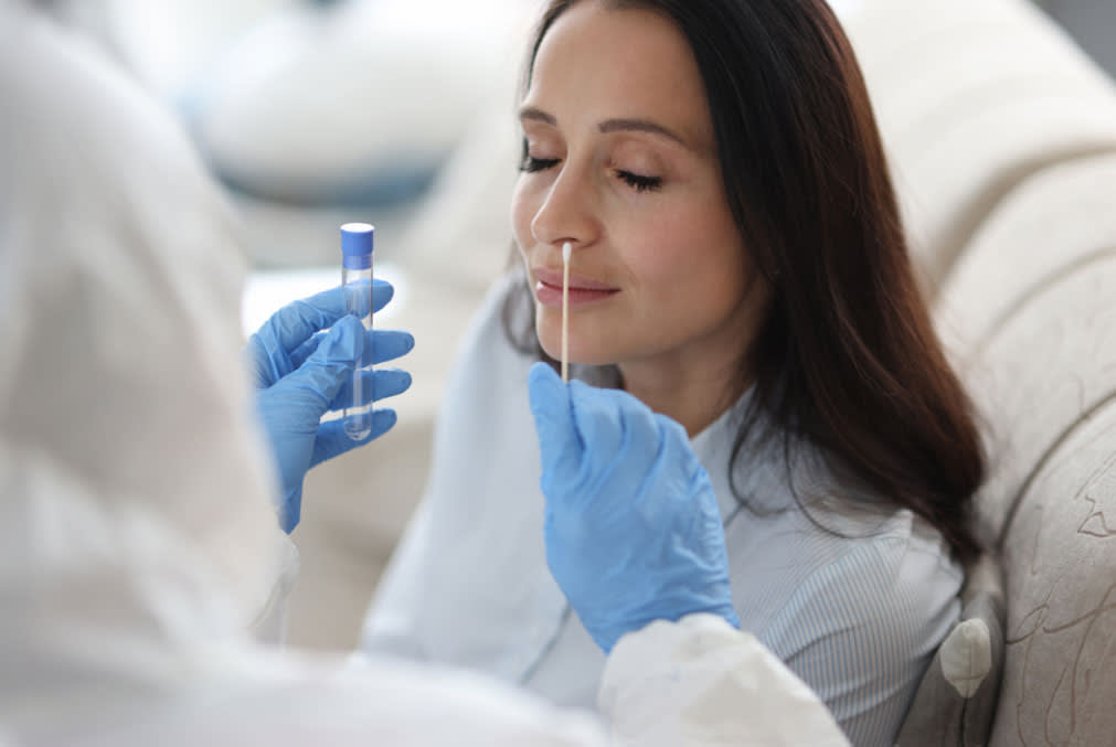 A lab technician in protective suit taking nose swab for COVID-19 diagnostic test at home.