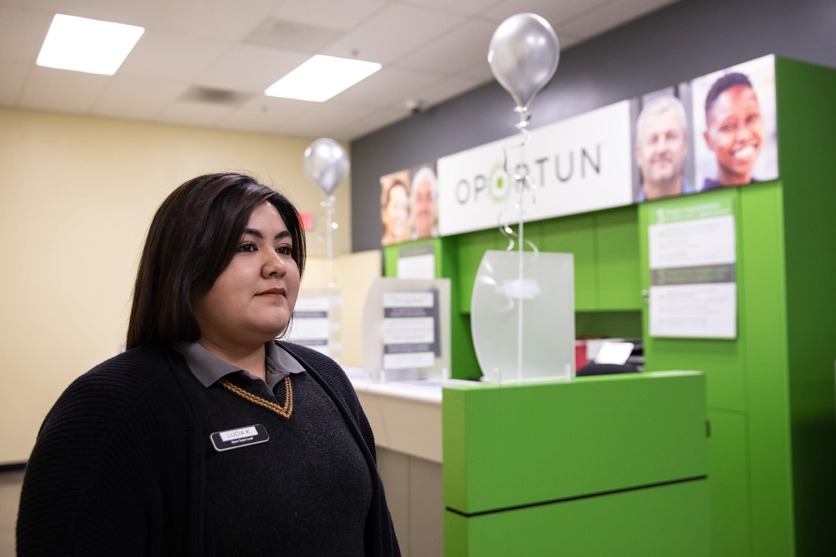 An Oportun employee stands in an Oportun loan agency with a thoughtful expression on her face.