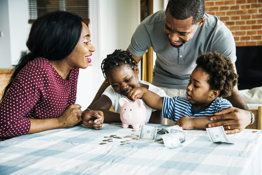 A mother and father teaching their son and daughter about saving money by filling a piggy bank with coins.
